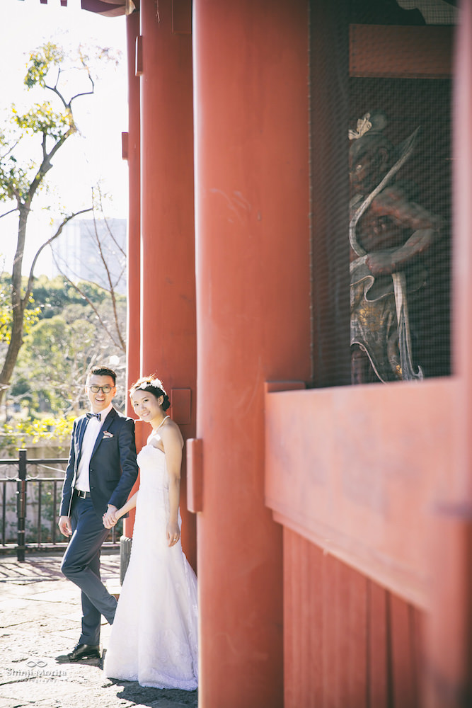 Pre-wedding photo near Tokyo tower with a couple posing underneath the red torii