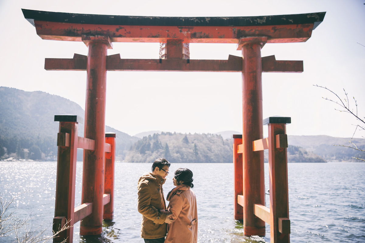 A couple looking at each other romantically in front of torii of Hakone shrine