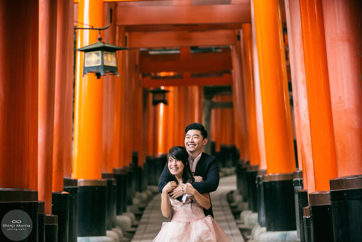 A couple cuddling and smiling inside red torii in Fushimi inari shrine in Kyoto