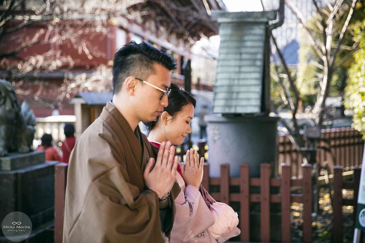 A couple praying at the temple in Asakusa wearing kimono