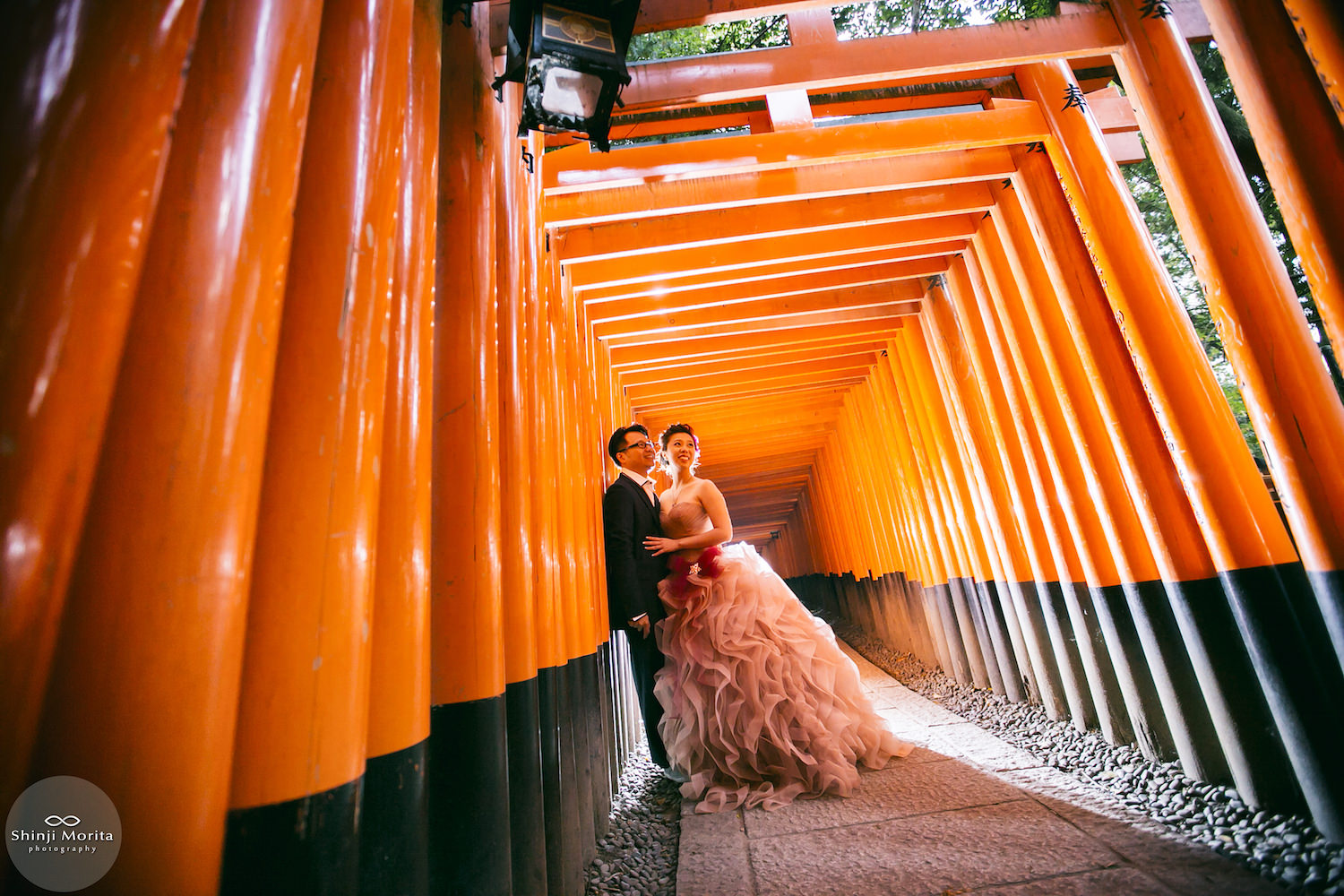 A couple cuddling inside the red torii at Fushimi inari shrine, Kyoto