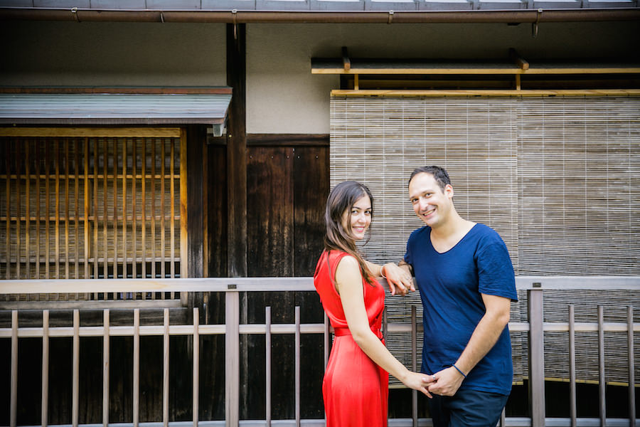 A couple posing in front of traditional wooden house in Gion for vacation photo with Yusuke HImi