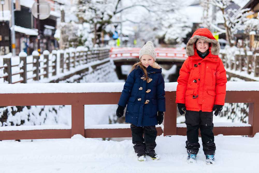 A boy and a girl posing in front of the bridge in snow looking warm