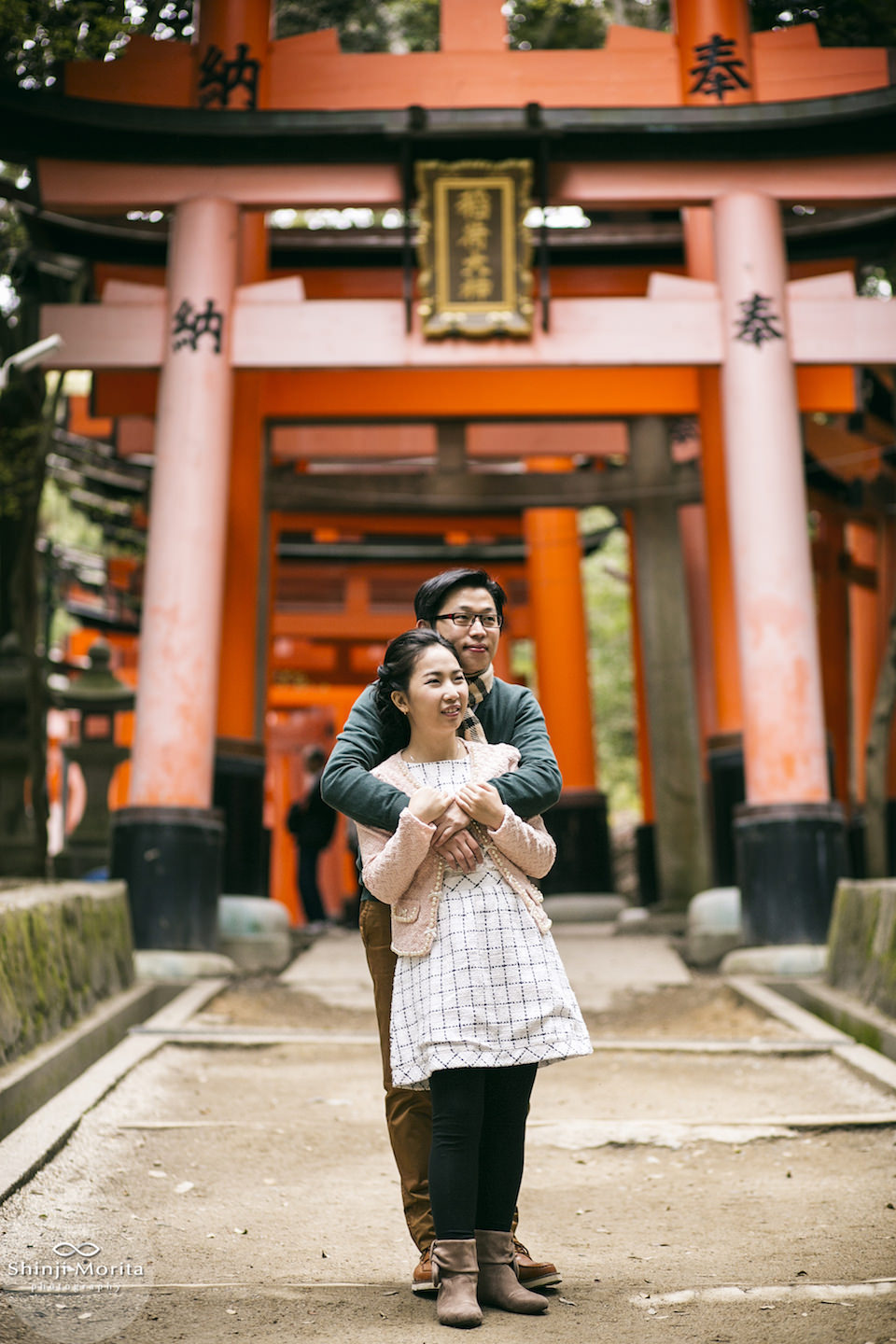 A couple hugging in front of Fushimi inari shrine in Kyoto