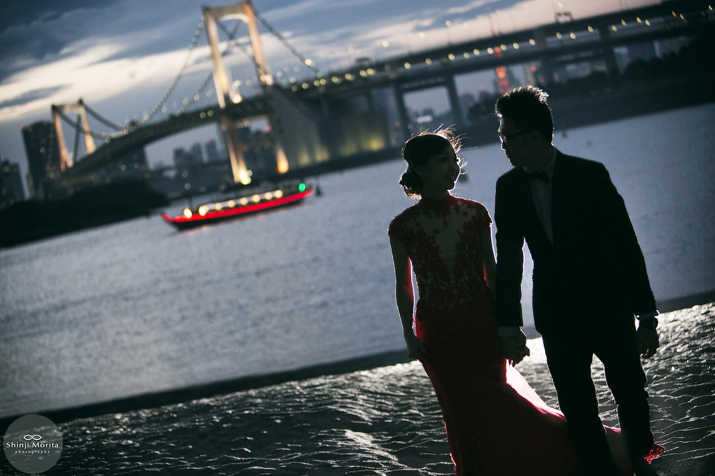 A couple walking along the Odaiba bay area holding hand with woman wearing a beautiful dress