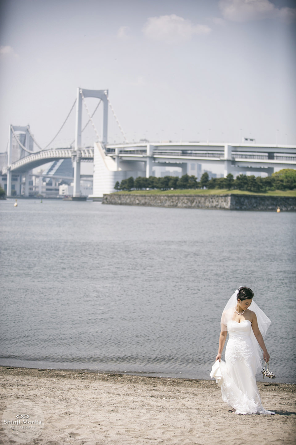 A woman dressed in wedding dress walking at the beach in Odaiba bay area
