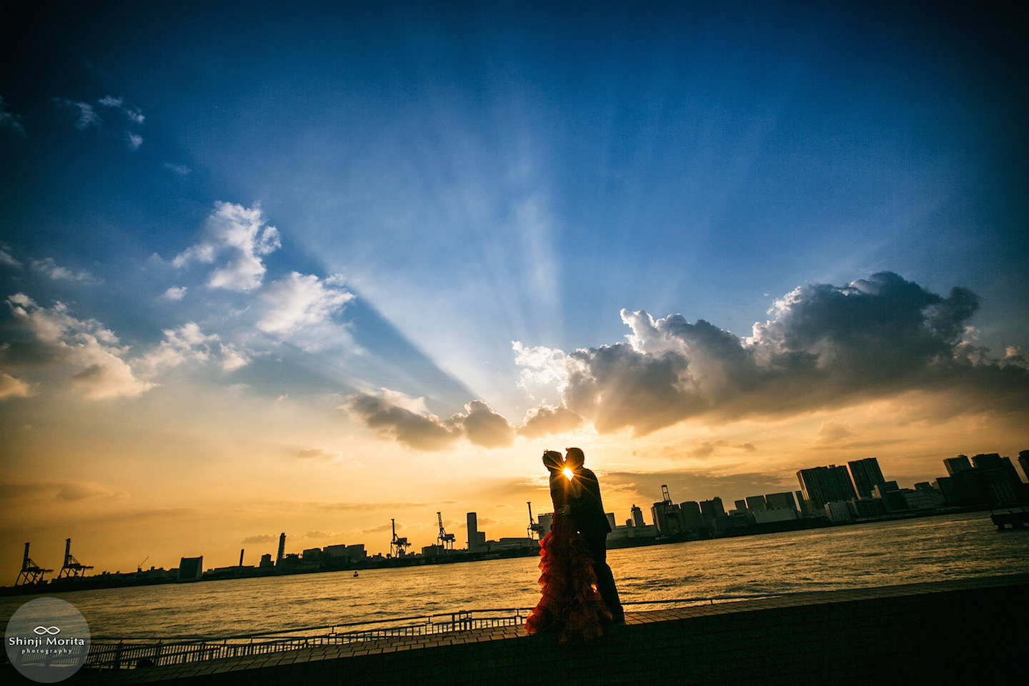 A couple kissing with a beautiful sunset for pre-wedding photo