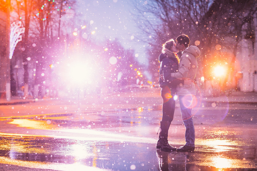 A couple kissing in snow in winter