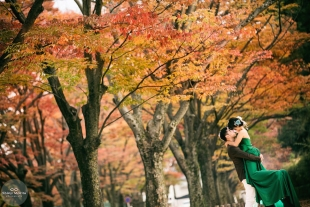 A couple kissing in Kyoto botanical garden in Autumn with woman wearing a green dress