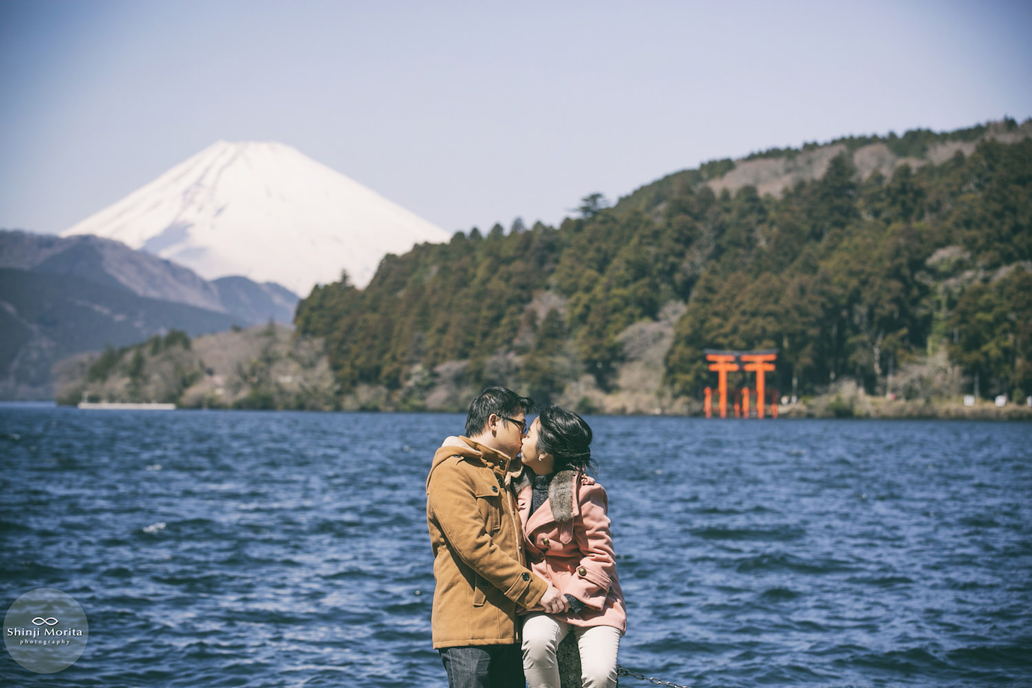 A couple kissing in Ashinoko lake in Hakone with Hakone shrine and Mt. Fuji in the background