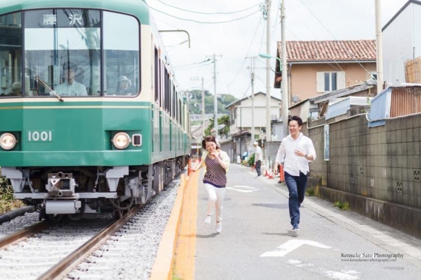 A couple running along the railway racing the train in Kamakura