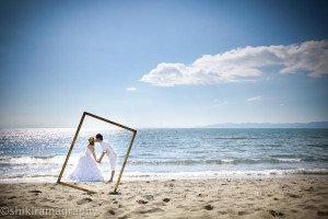 Pre-wedding photo of a couple kissing on the beach as they fit into a photo frame