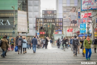 A couple standing in the middle of the crossing with woman wearing wedding dress for pre-wedding photo