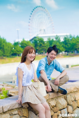 A couple holding hands and smiling at the camera with ferris wheel in the background