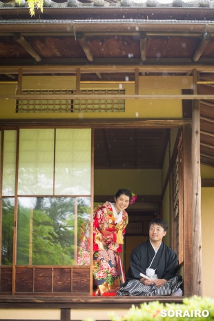 A couple looking at the camera while wearing kimono inside the authentic wooden house for pre-wedding photo
