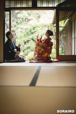 A couple playing with Japanese paper balloon by the garden wearing kimono for pre-wedding photo