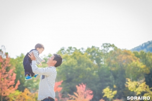 A father holding his son up in the air in the park in Autumn