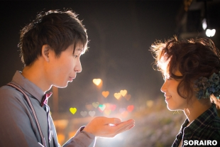 A couple looking at each other romantically while blowing a heart shaped lights