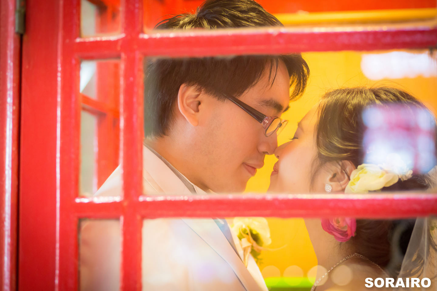 cA couple looking at each other romantically inside the telephone box with woman wearing wedding dress for pre-wedding photo