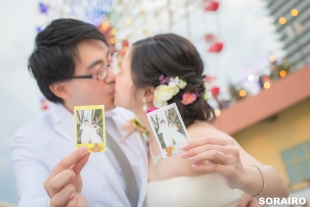 A couple kissing while holding their photos in hand for pre-wedding photo