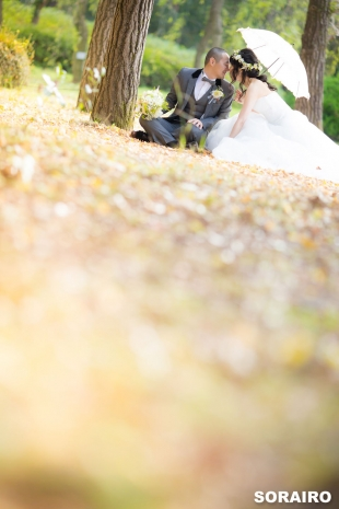 A couple kissing with woman wearing wedding dress for pre-wedding photo in Kyoto