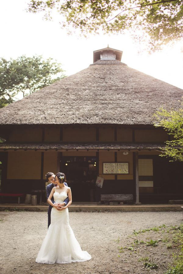 A couple cuddling in front of traditional Japanese house in Hakone for pre-wedding photo with CHiKA