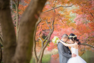 A couple in love posing in the park in Kyoto in Autumn with woman wearing wedding dress for pre-wedding photo