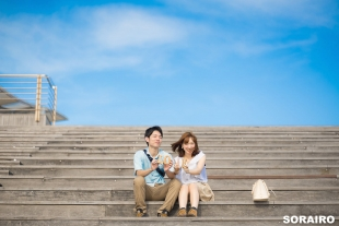 A couple holding love sign on a sunny day by bay side area