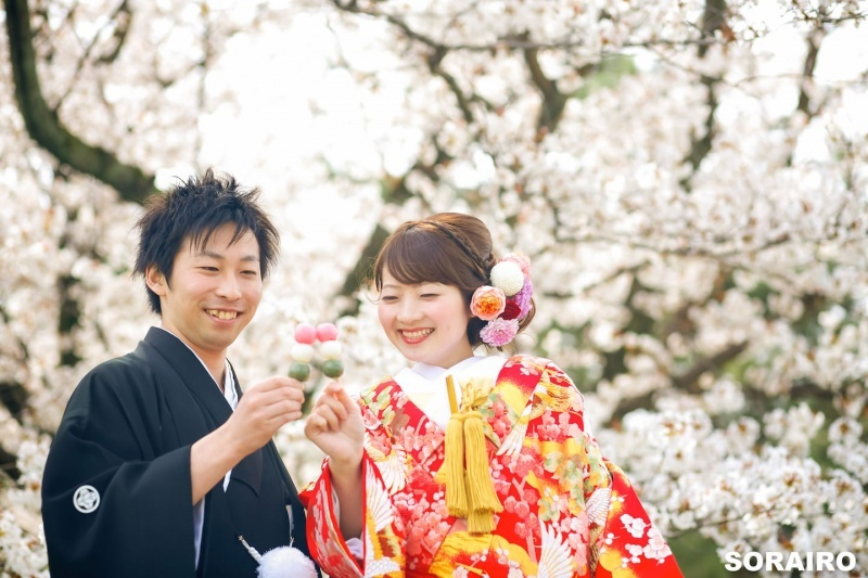 A couple dressed in Kimono in front of cherry blossom holding Japanese sweet for pre-wedding photo