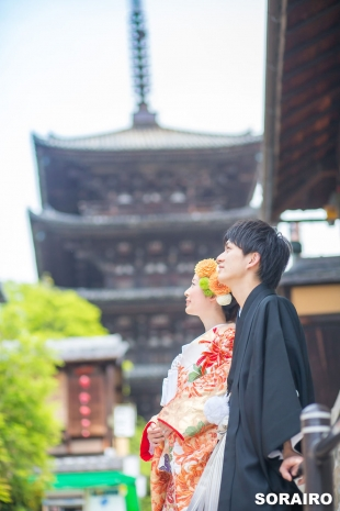 A couple looking up into the blue sky wearing kimono in front of Toji temple in Kyoto for pre-wedding photo