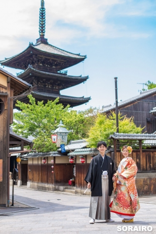 A couple posing in front of the camera wearing kimono with Toji temple in the background in Kyoto for pre-wedding photo