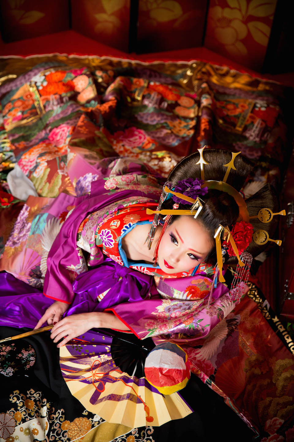 Sexy oiran laying dowon on the tatami floor with beautiful Kimono with a lot of hair accesories. This artistic oiran photo was taken by Studio Esperanto for make-over photo shoot in Kyoto Japan.