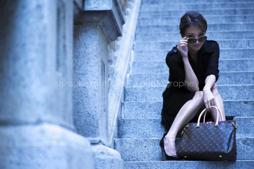 A woman sitting on the stairs posing for solo vacation photo