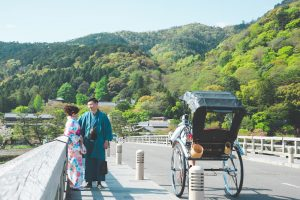 Vacation photo of a couple posing at Togetsukyo bridge in Arasshiyama, Kyoto