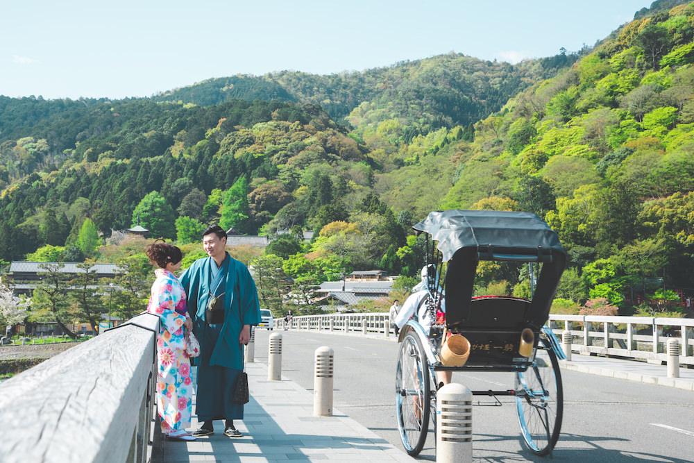Vacation photo of a couple posing at Togetsukyo bridge in Arasshiyama, Kyoto