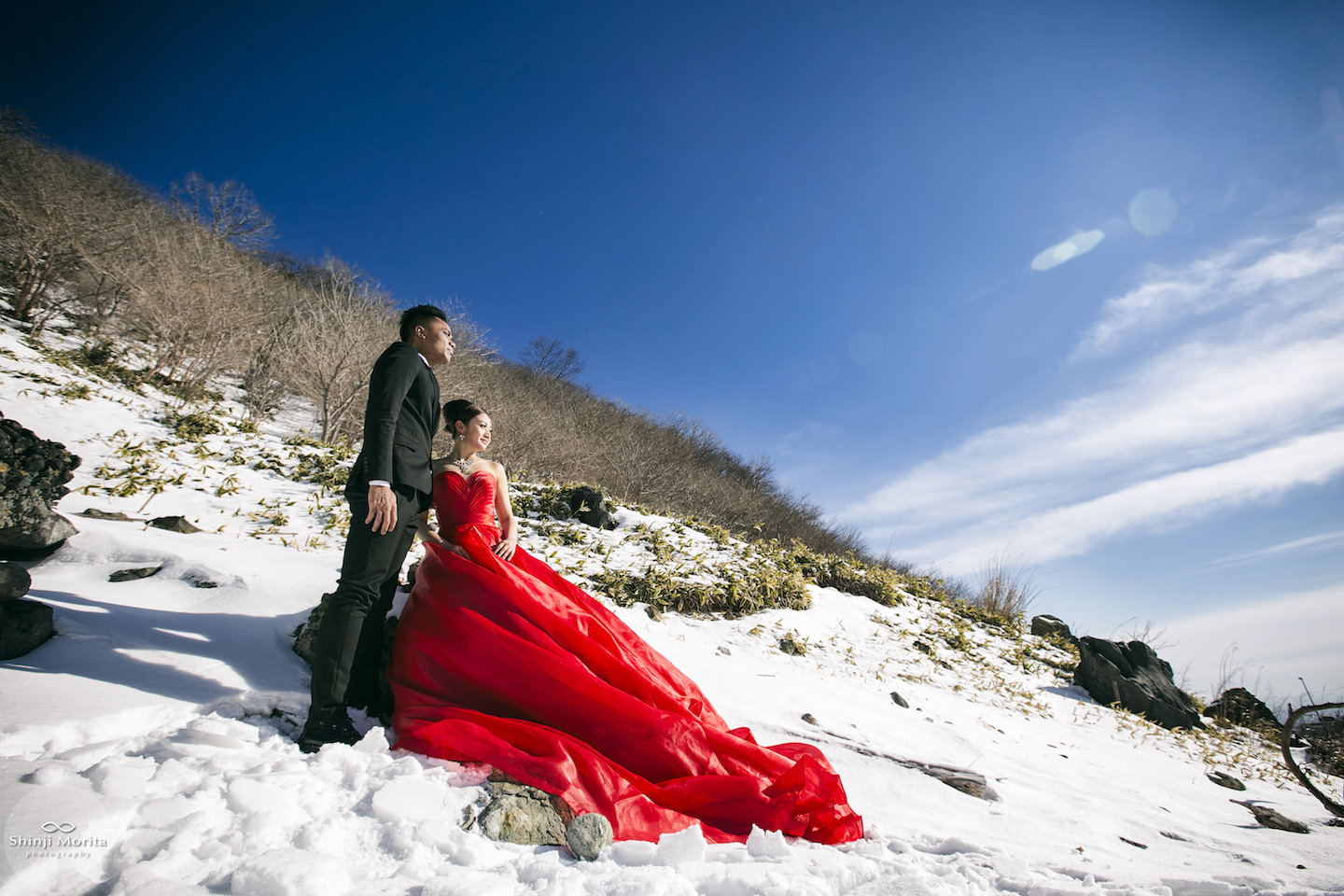 A couple posing with snow in the background with woman wearing a beautiful red dress