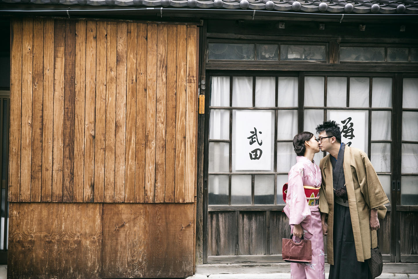A couple kissing in front of an authentic Japanese wooden house with couples wearing kimono in Nezu, Tokyo
