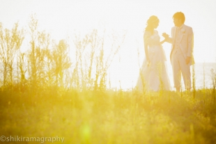 A couple looking at each other as the sun goes down with woman wearing a wedding dress for pre-wedding photo