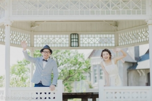 A couple waving at the camera with woman wearing a cute white dress for pre-wedding photo