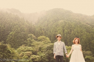 A couple holding hands in front of a green forest