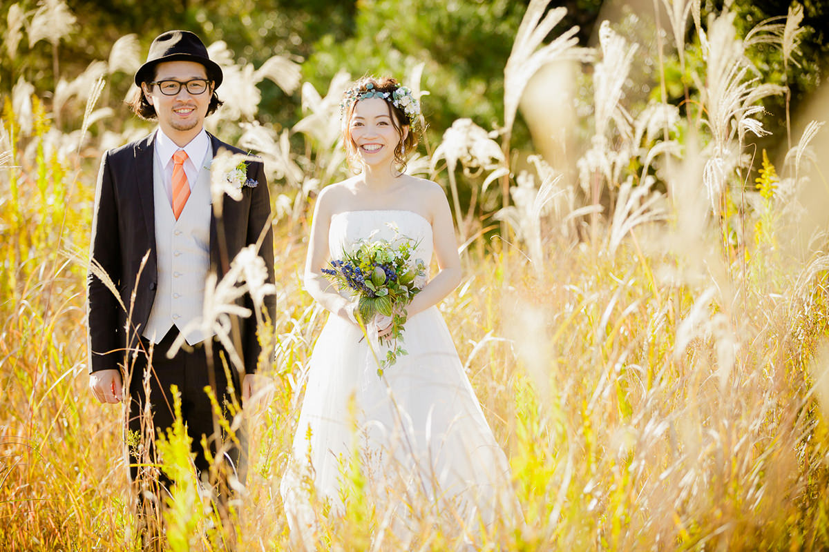 A couple posing in front of the camera standing in the field in Autumn with woman wearing a wedding dress for pre-wedding photo
