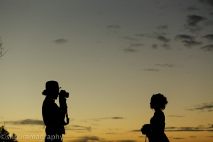 A man taking picture of a woman wearing a dress during sunset