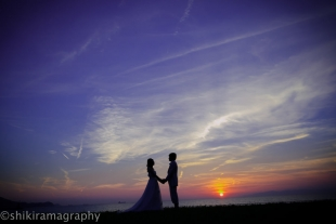 A couple holding hands looking at each other romantically as the sun goes down by the beach with woman wearing a dress