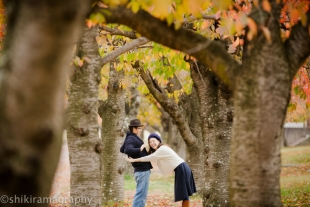 A couple being playful in the park in Autumn