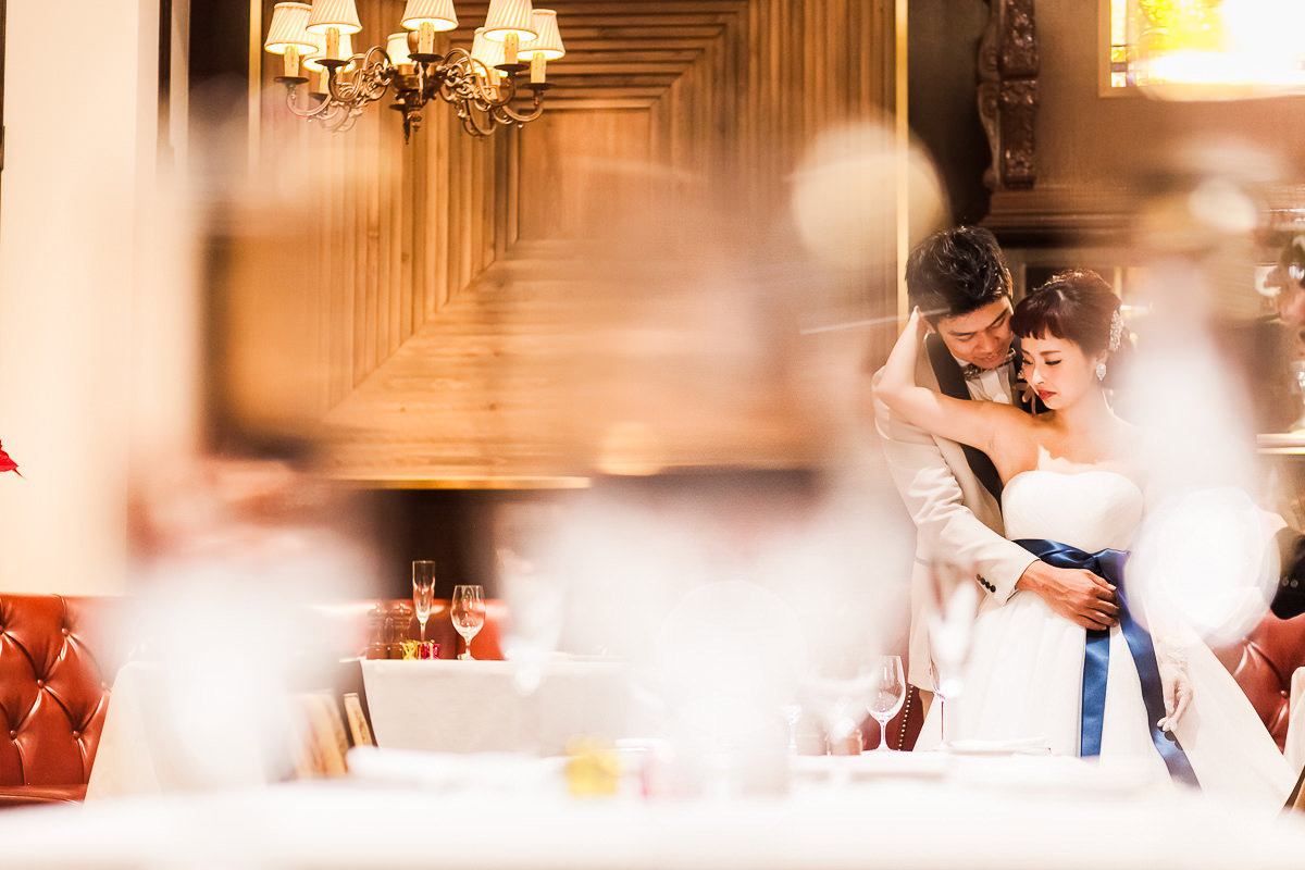 A couple hugging in a restaurant with woman wearing a beautiful wedding dress for pre-wedding photo