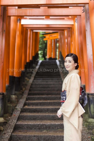 A woman dressed in kimono inside red torii