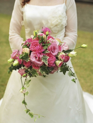 A woman holding a flower bouquet dressed in wedding dress