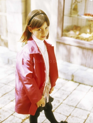 A girl walking along the street wearing a red jacket