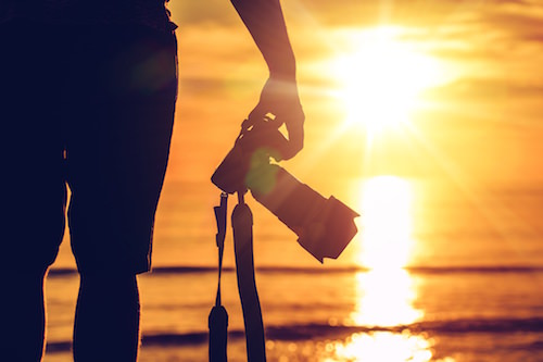 Photographer standing looking at the sunset at the beach