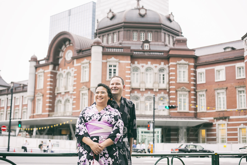 Pre-wedding photo of a couple posing and smiling at the camera in front of Tokyo station